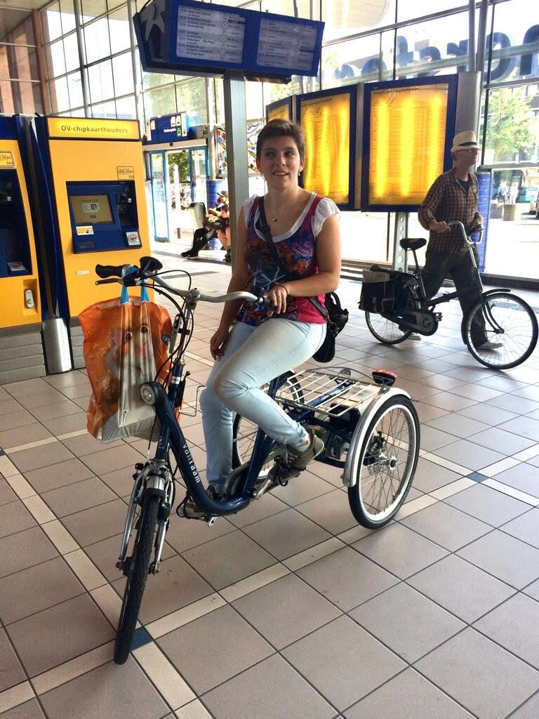 Foto van kernlid Cynthia op haar driewieler in een station.