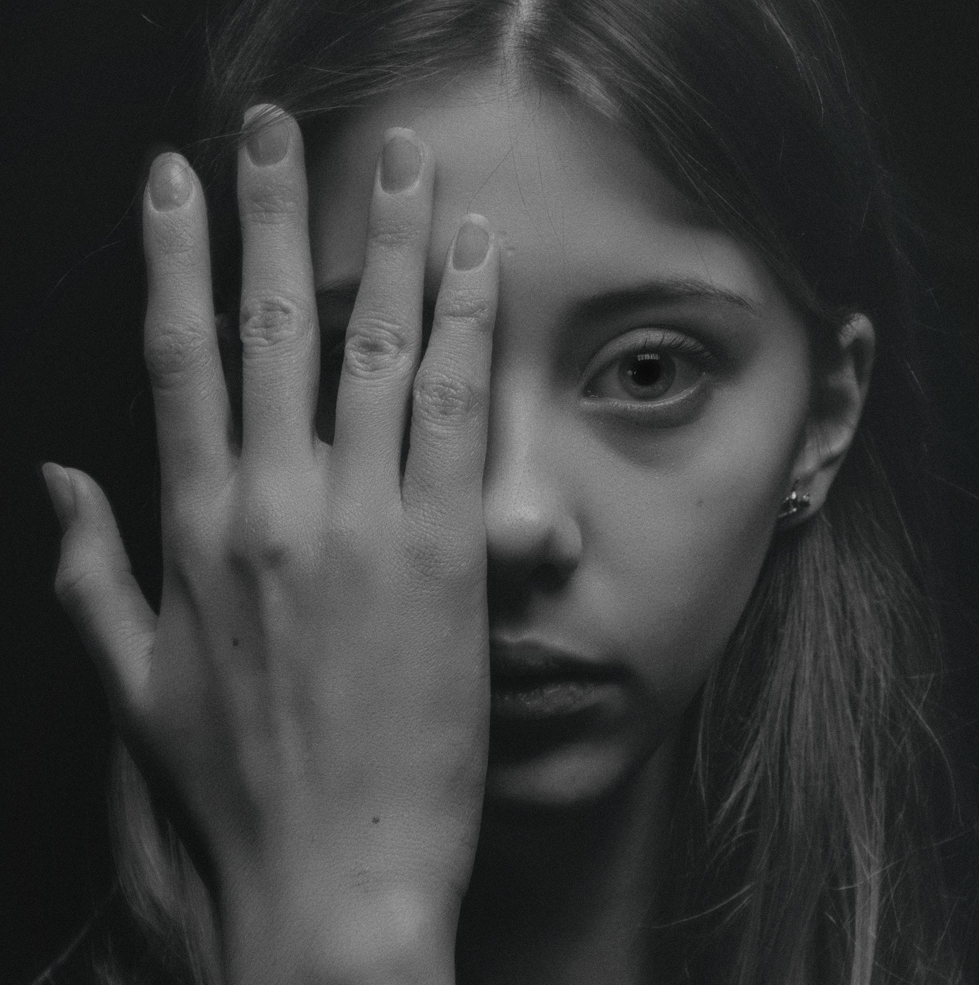 Beeldbankfoto van jonge vrouw die haar oog afdekt met haar hand. Photo by Alexander Krivitskiy from Pexels.